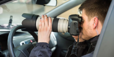 Close-up Of A Young Man Inside Car Photographing With Slr Camera