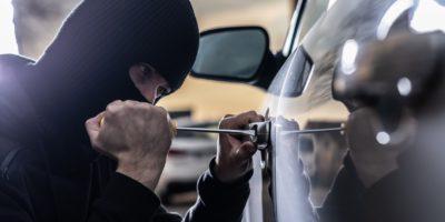 Car thief opening stolen car doors. Car thief, car theft